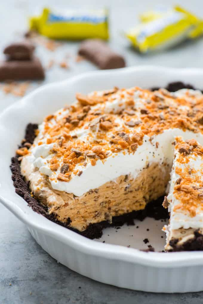 whole butterfinger pie with one slice removed in white pie pan on gray background