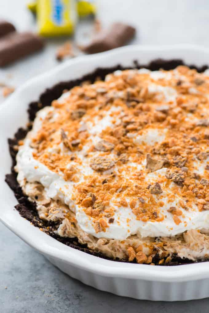 whole butterfinger pie in white pie pan on gray background