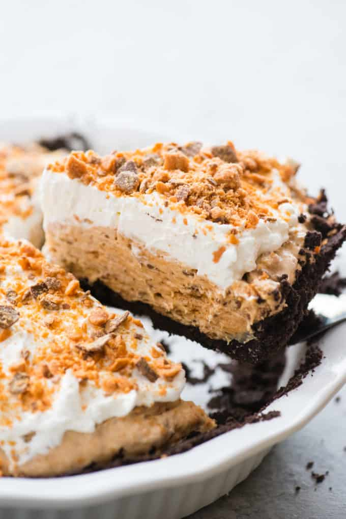 slice of butterfinger pie on spatula being removed from white pie pan