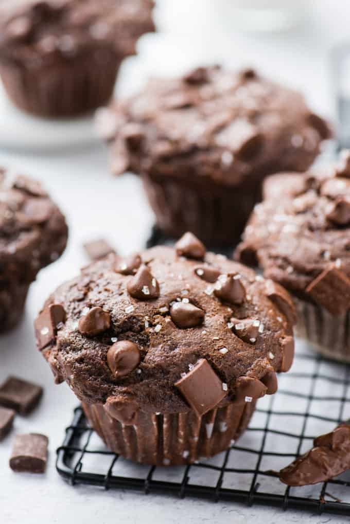 chocolate muffin on black wire rack with more muffins in the background