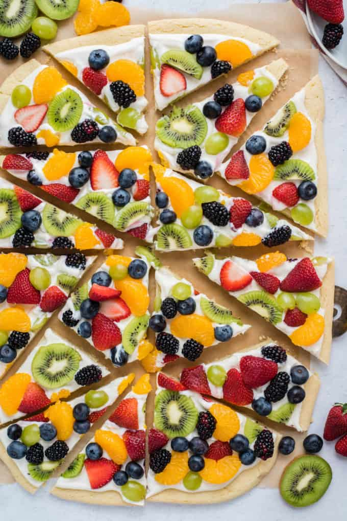 a whole fruit pizza cut into triangle slices with strawberries, blueberries, mandarin oranges, kiwis and grapes on brown parchment paper