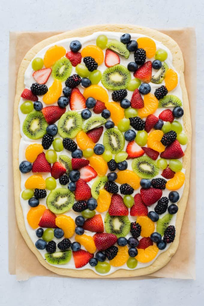 a whole fruit pizza with strawberries, blueberries, mandarin oranges, kiwis and grapes on brown parchment paper