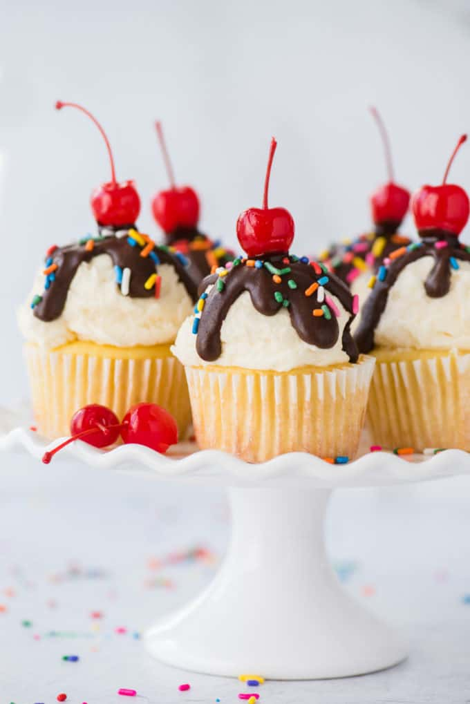 ice cream cupcakes displayed on white cake stand on white background