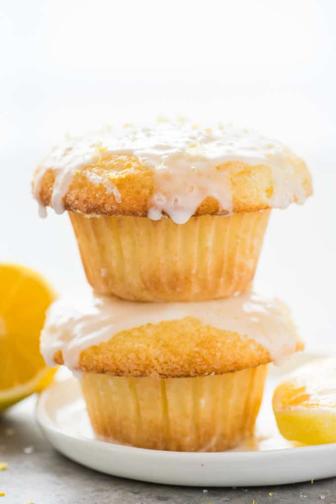 two lemon muffins with glaze stacked on each other on white plate on white background
