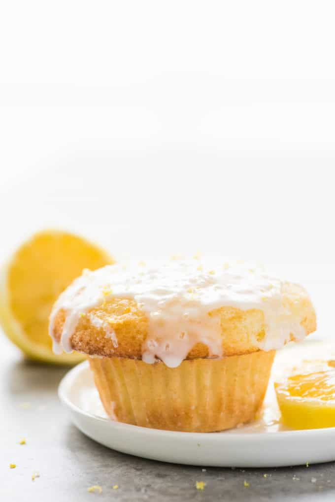 single lemon muffin with glaze on white plate on white background