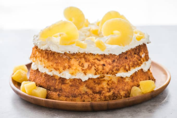 whole angel food cake topped with whipped cream and pineapple slices on wood serving tray on white background