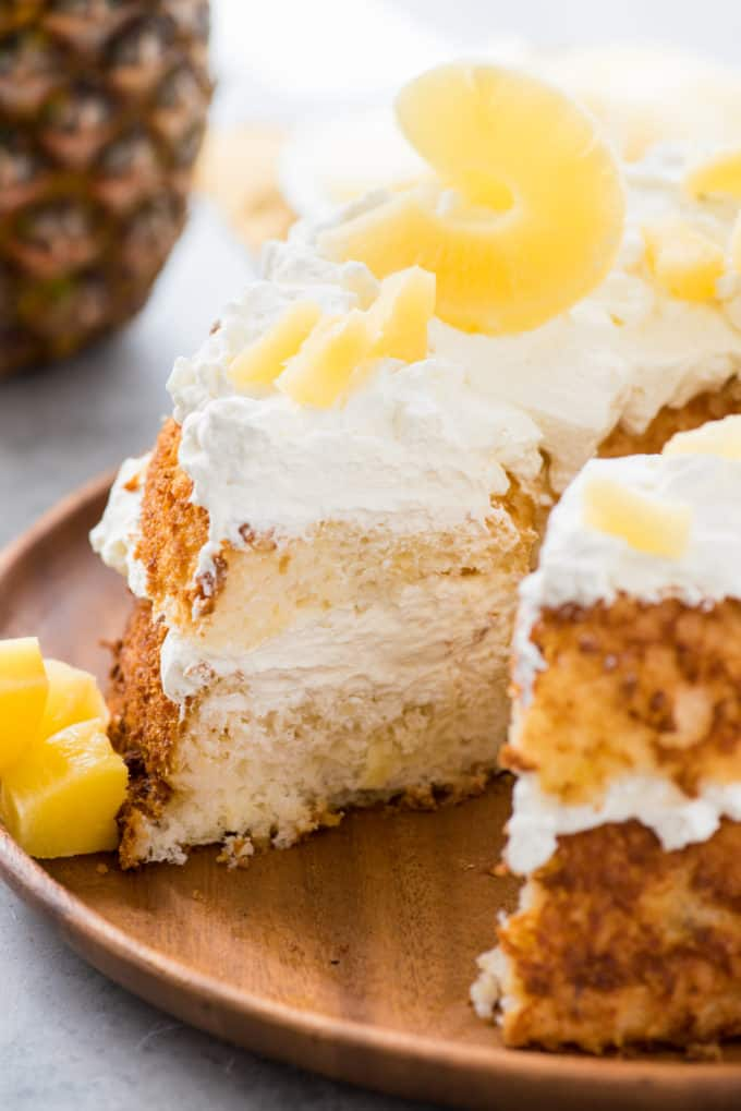 angel food cake with slice removed topped with whipped cream and pineapple slices on wood serving tray on white background