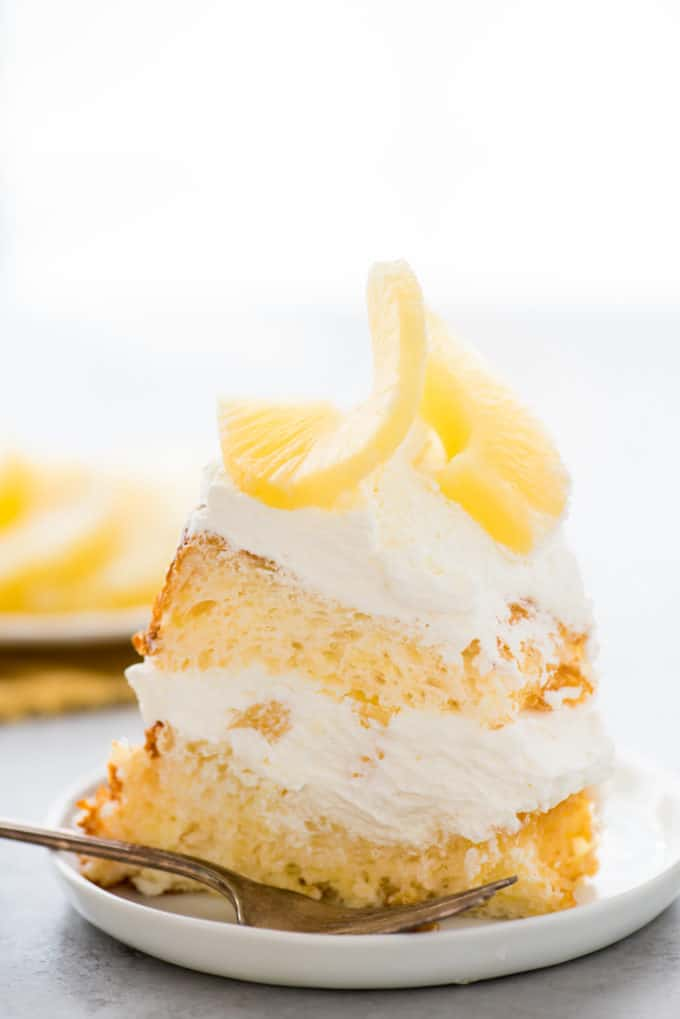 slice of pineapple angel food cake with whipped cream and pineapple on white plate on white background