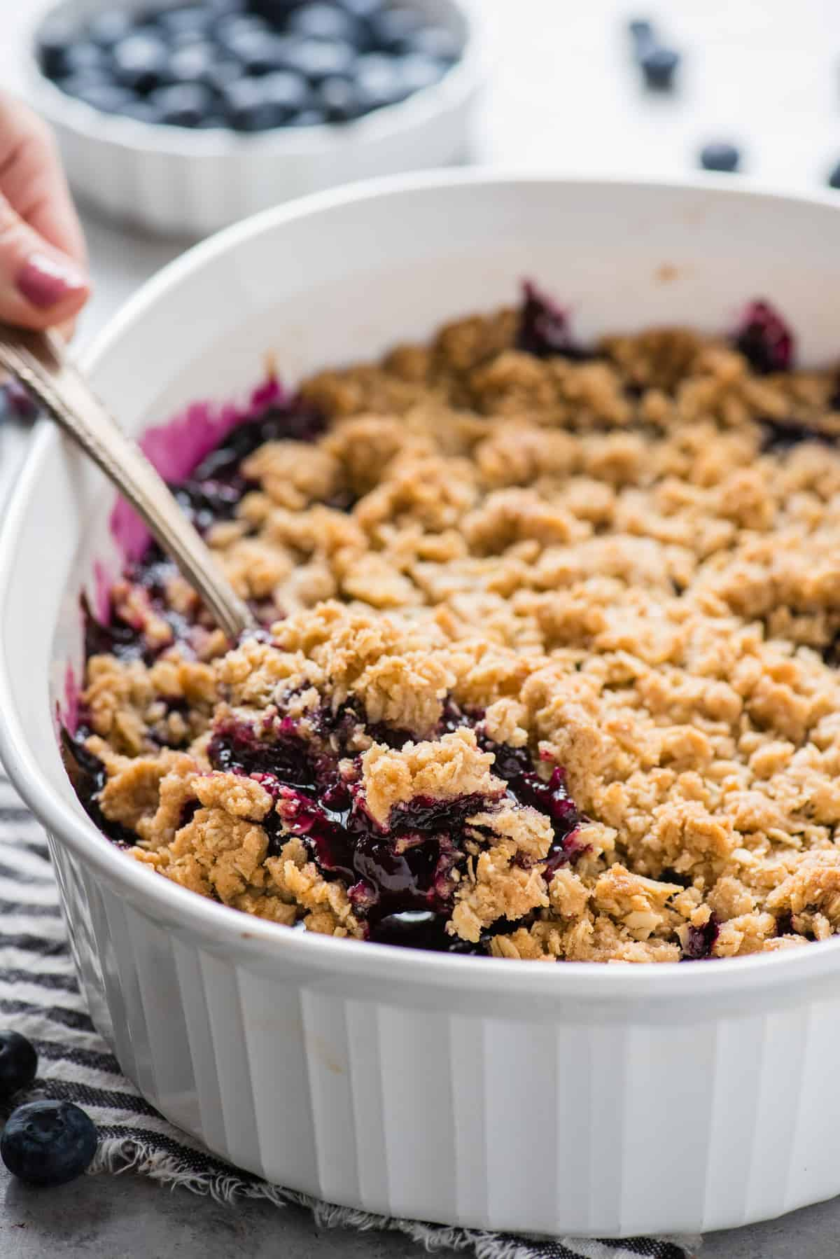 blueberry crisp in a white baking dish with a metal spoon