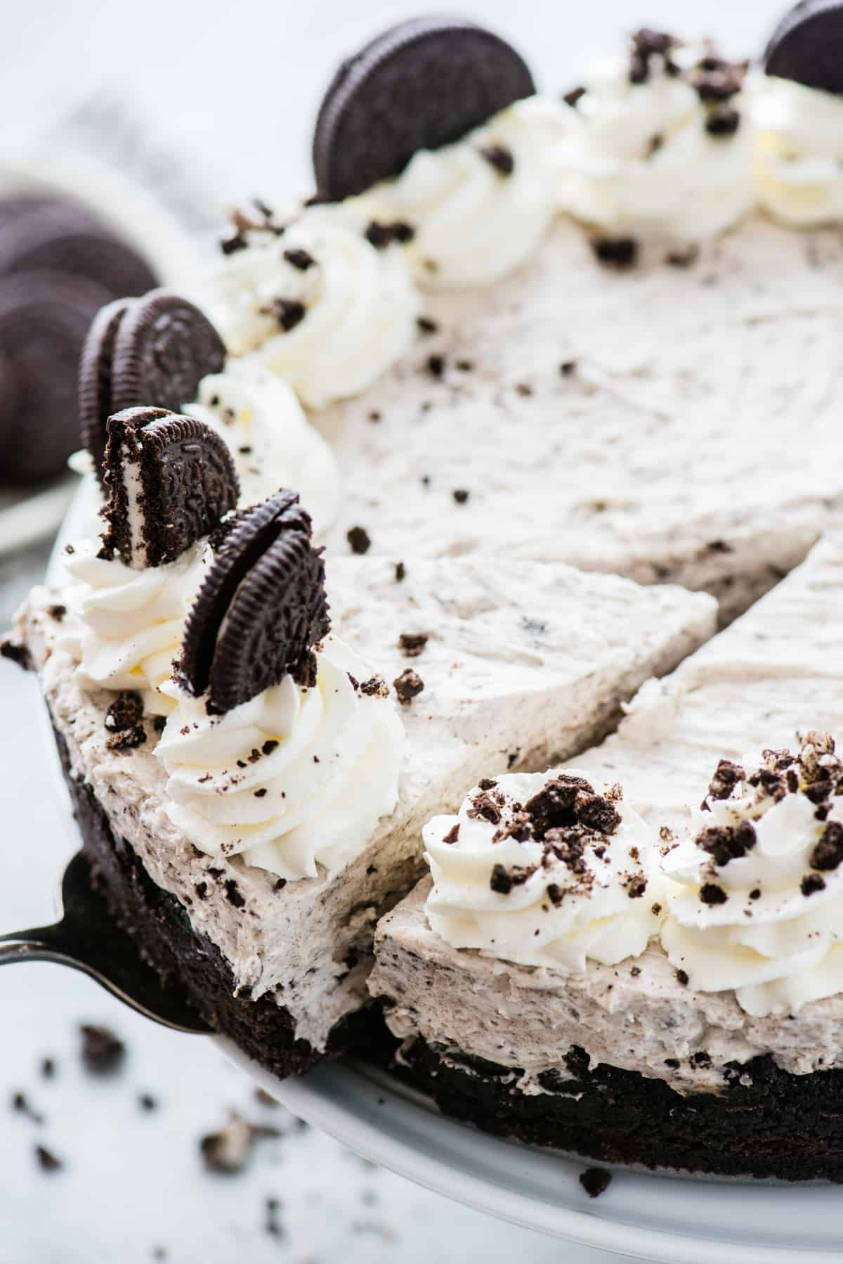 whole no bake oreo cheesecake topped with whipped cream swirls and oreo pieces on white background