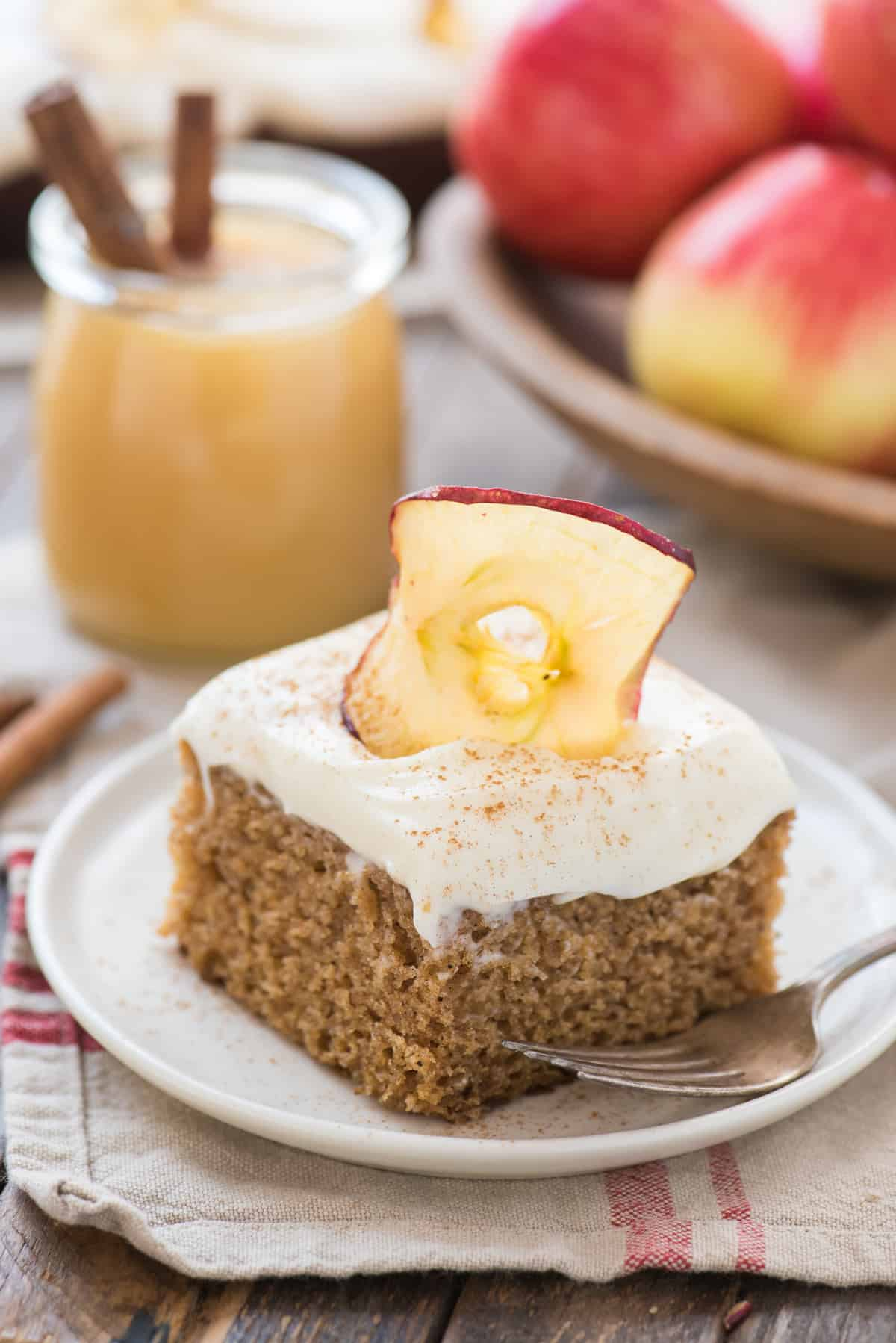slice of applesauce cake with cream cheese frosting on white plate with apples in the background