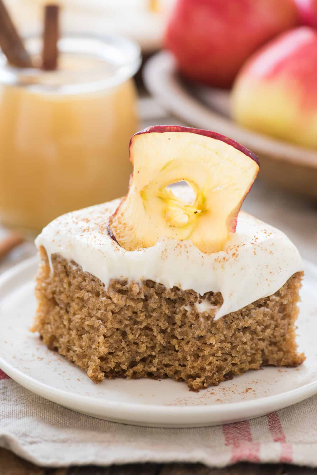 slice of applesauce cake with cream cheese frosting with bite removed on white plate