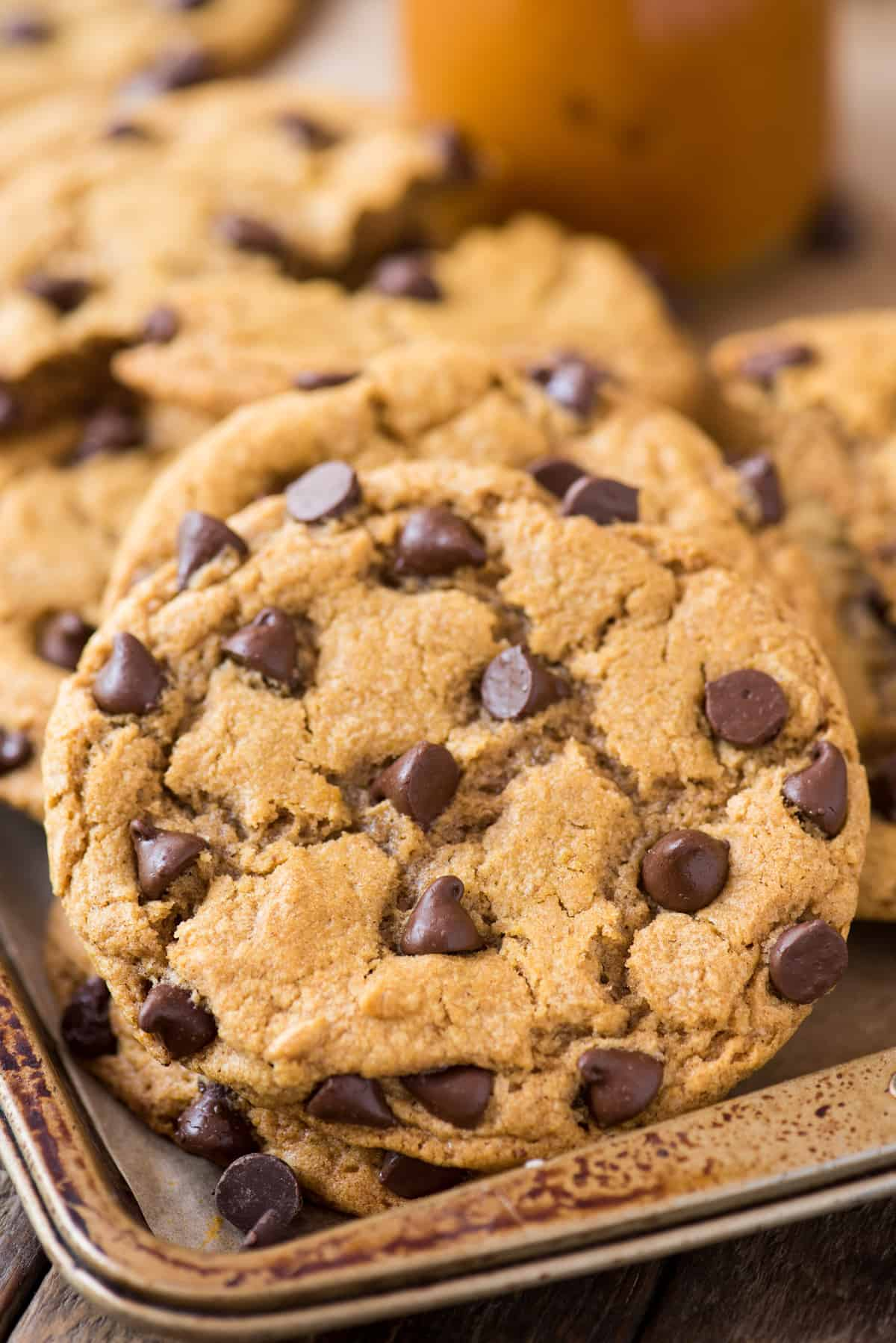 close up of pumpkin chocolate chip cookie on metal baking sheet