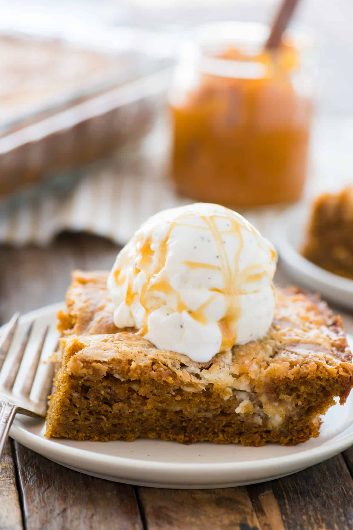Slice of pumpkin earthquake cake on white plate with scoop of vanilla ice cream on top