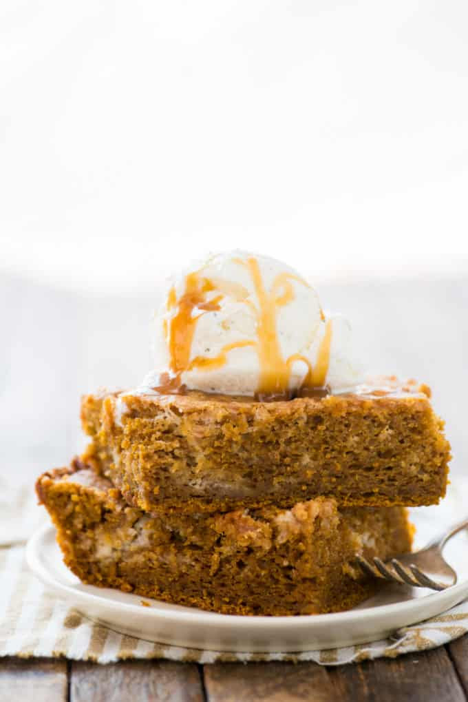 Two slices of pumpkin earthquake cake stacked on top of each other on white plate with scoop of vanilla ice cream on top