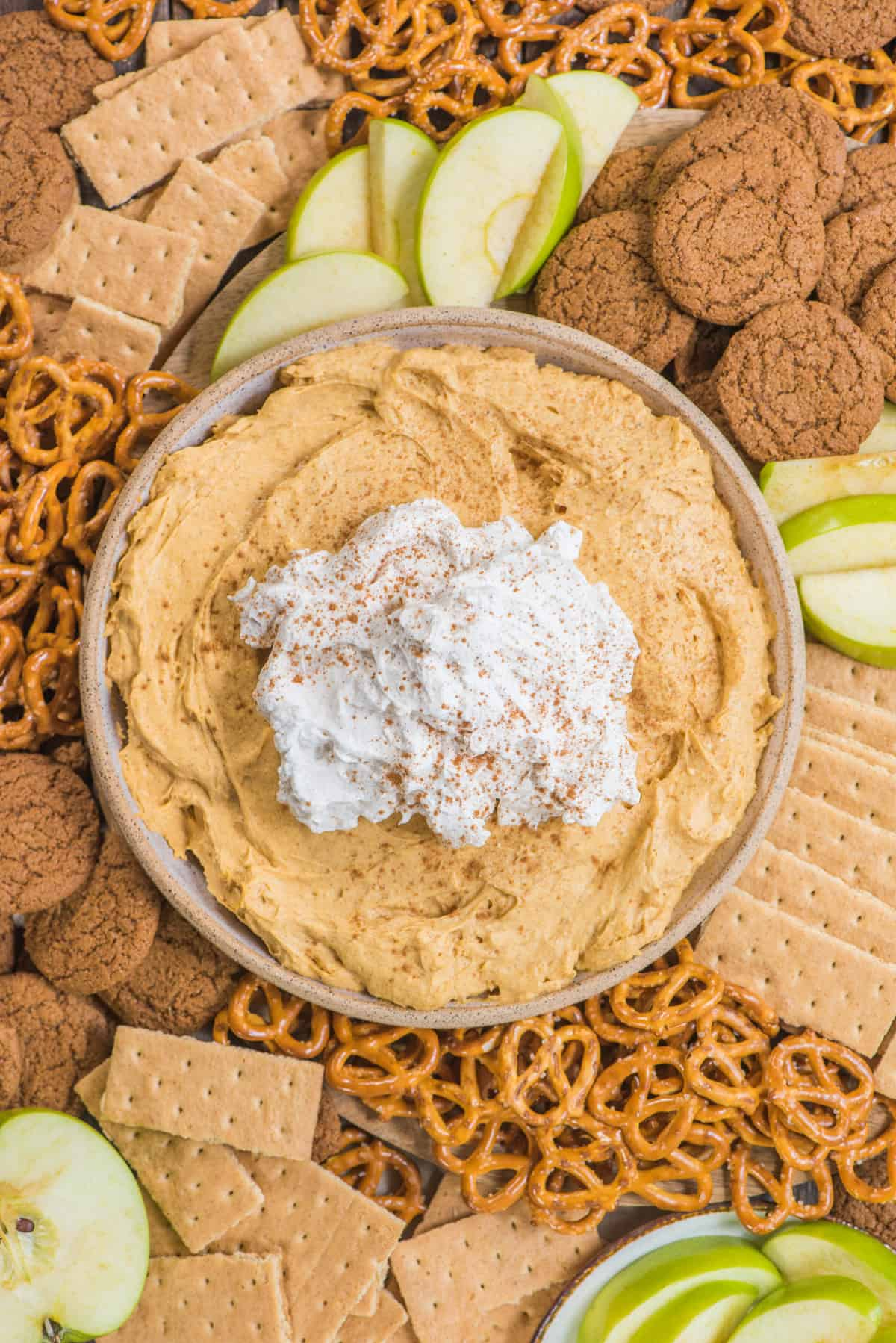 pumpkin dip with whipped cream topping in a bowl surrounded by piles of pretzels, gingersnaps, graham crackers and green apple slices