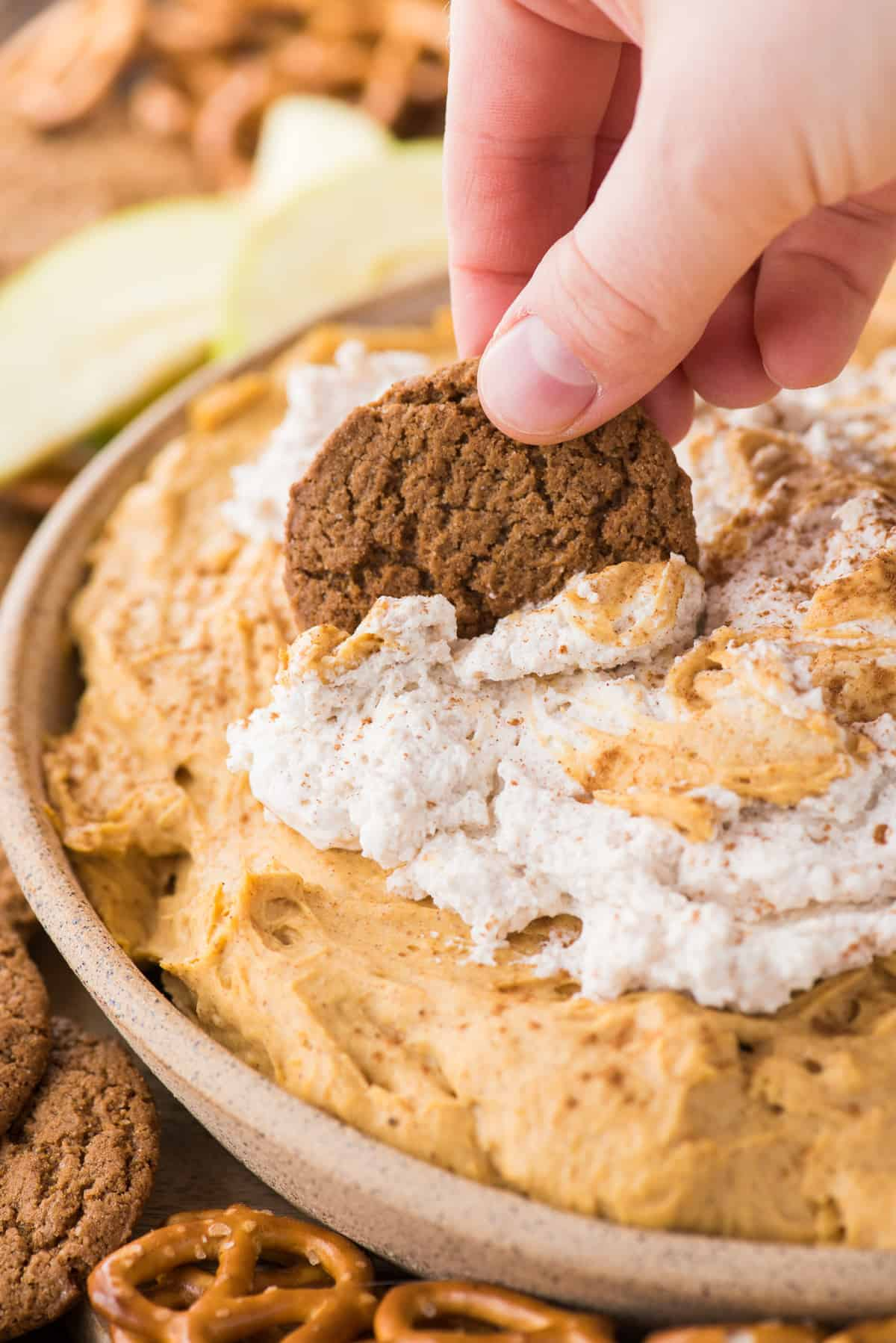 pumpkin dip with whipped cream topping in a bowl with hand dipping gingersnap cookie into dip