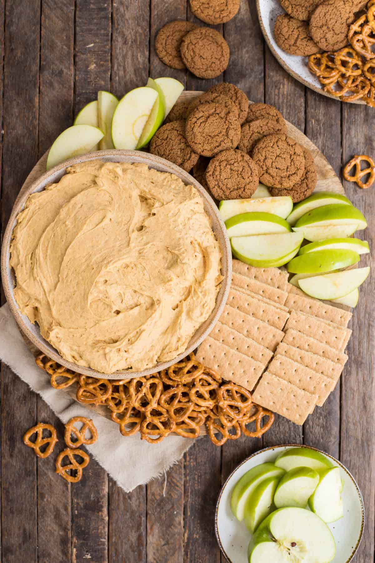 pumpkin dip in a bowl surrounded by piles of pretzels, gingersnaps, graham crackers and green apple slices on wooden background