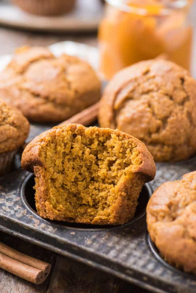pumpkin muffin with bite taken out arranged in metal muffin pan