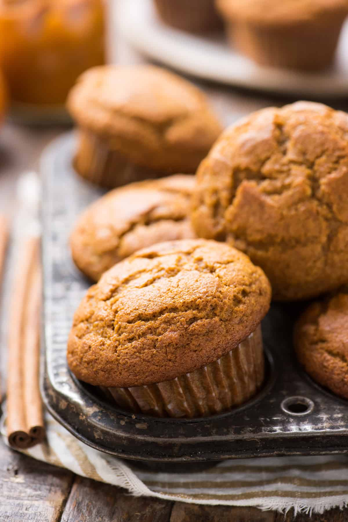 pumpkin muffins arranged in metal muffin pan with cinnamon stick on the left side