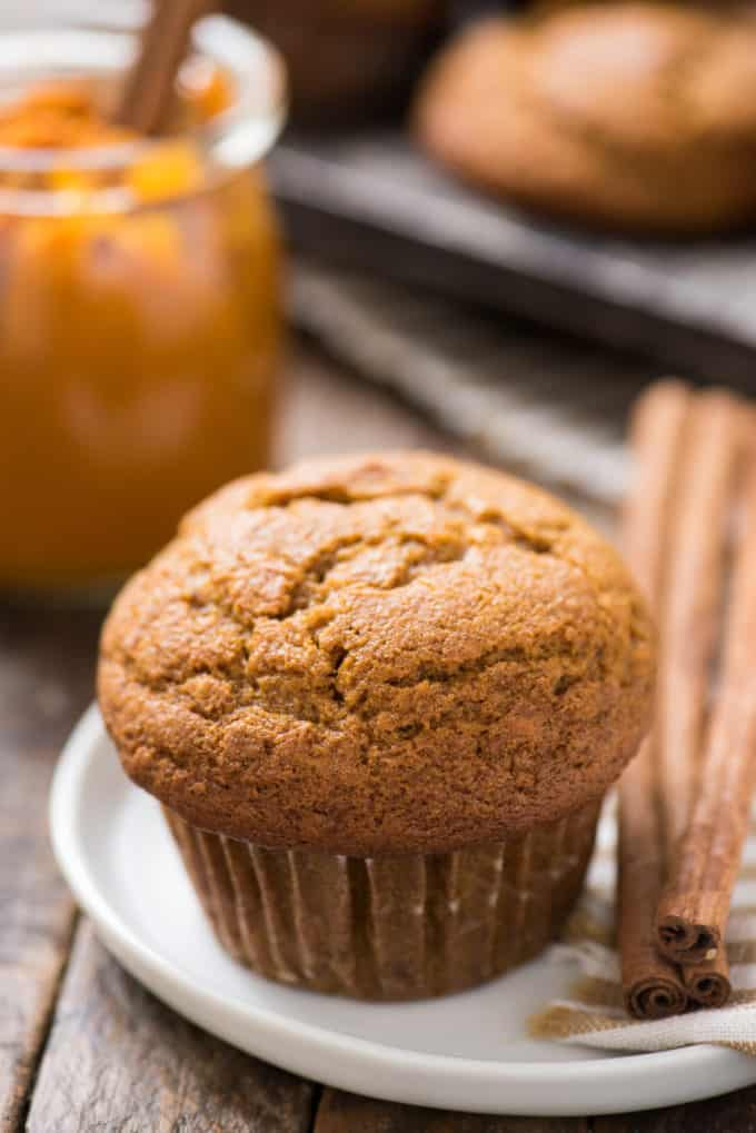 pumpkin muffin on white plate with cinnamon sticks on the right side